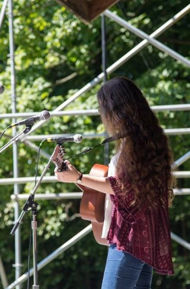 Image Description: Lily Mae playing guitar on an outdoor stage, facing away from the camera.