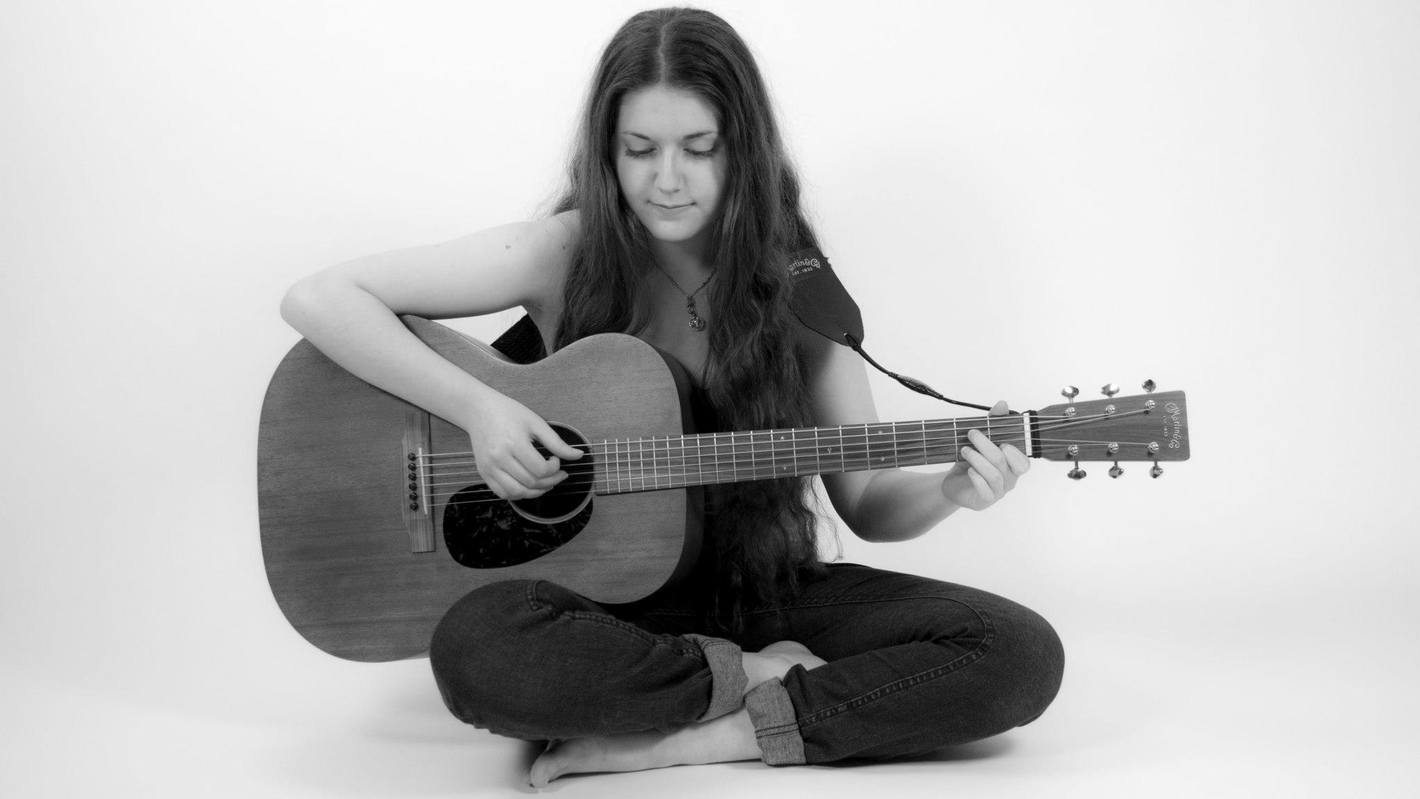 [description] Black and white photo of Lily Mae sitting cross legged and playing guitar